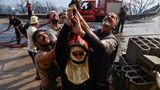 Kabylei, Algerien. Mit aller Kraft stemmen sich Feuerwehrleute und freiwillige Helfer gegen die Brände in dem nordafrikanischen Staat. Die Männer versuchen hier, die Flammen, die über ihnen einen Haus erfasst haben, zu löschen. Seit Tagen wüten vor allem östlich der Hauptstadt Algier verheerende Brände, die Feuerwehren sind unzureichend ausgerüstet. Mindestens 77Menschen sind bisher ums Leben gekommen.