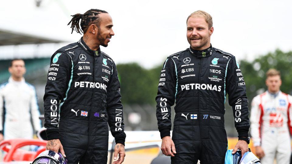 Lewis Hamilton und Valtteri Bottas posieren vor ihren Rennwägen