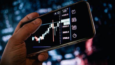 Inflation: Ein Smartphone-Display zeigt schwankende Aktienkurse