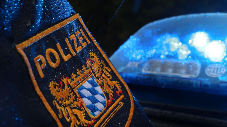 Auf einem regennassen Ärmel prangt das Wappen der Polizei Bayern, während dahinter ein Blaulicht die Dunkelheit erhellt