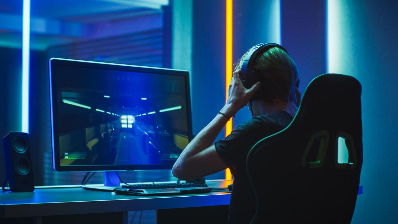 Ein Zocker sitzt vor seinem 144-Hz-4K-Monitor und setzt sich ein Headset auf.