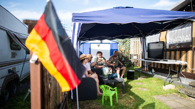 Menschen sitzen um einen Tisch auf einem Campingplatz