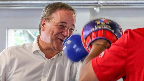 Ein älterer weißer Mann mit grauem Seitenscheitel steht in weißem Hemd und blauen Boxhandschuhen im Ring