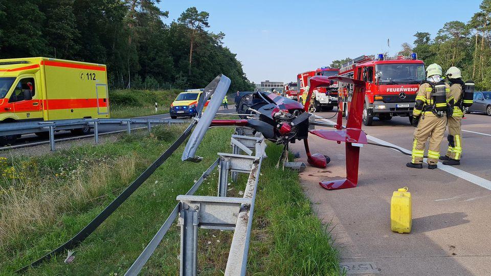 Ein roter Hubschrauber liegt seitlich auf dem Standstreifen einer Autobahn. Die Rotorblätter sind verbogen