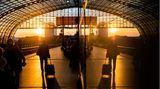Ein Fahrgast der Bahn geht über einen Bahnsteig und spiegelt sich im Glas einer Vitrine