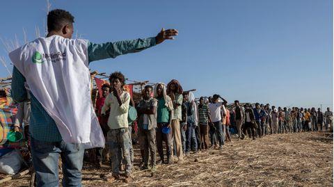 Ein Mitarbeiter einer muslimischen Hilfsorganisation koordiniert die Ankunft von Flüchtlingen in einem Camp nahe der äthiopisch-sudanesischen Grenze