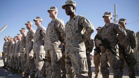 US-Soldaten in grauen Tarnfleck-Uniformen stehen auf einem staubigen Exerzierplatz in Reih und Glied