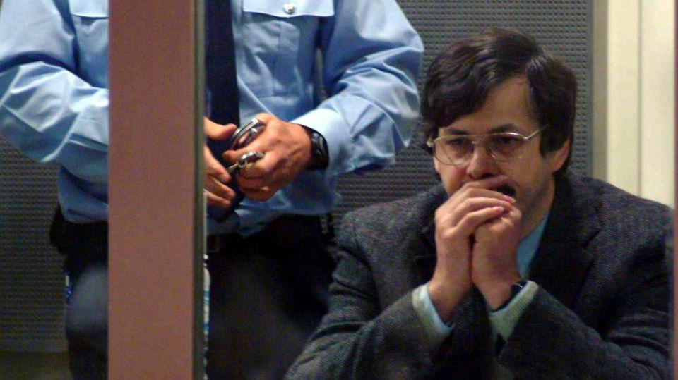 Ein bieder wirkender Mann mit schwarzem Seitenscheitel und silberner Brille sitzt mit Händen vor dem Mund vor Gericht