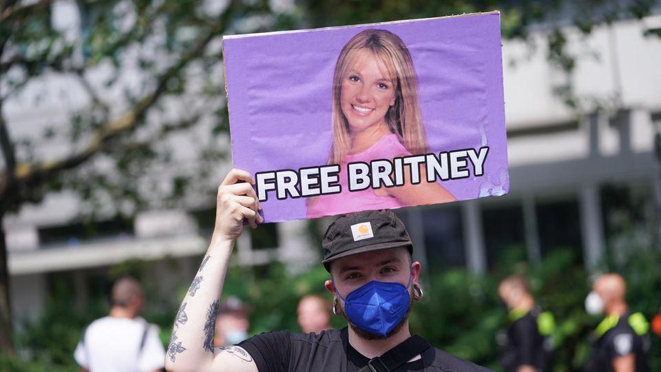 Eine Demonstrantion hält ein Schild mit dem Schriftzug Free Britney hoch