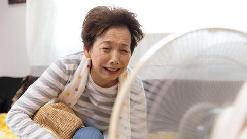 Eine ältere Dame kühlt sich vor einem Ventilator ab