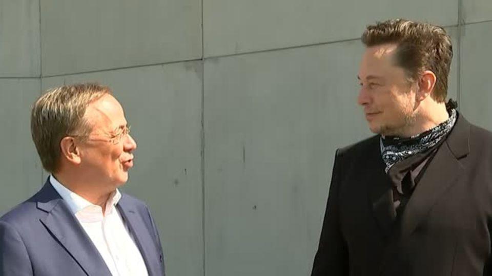 Vor einer Stahlbetonmauer stehen ein kleinerer weißer Mann im Anzug und ein größerer ganz in schwarz