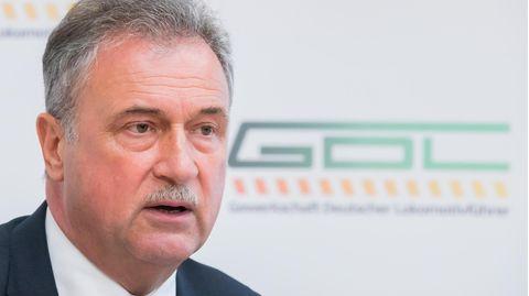 Ein älterer weißer Mann mit grauem Mittelscheitel und Schnauzbart sitzt im Anzug vor einer weißen Wand mit grünem GDL-Logo
