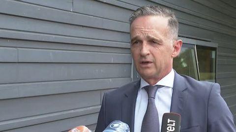 Ein weißer Mann mit angegrauten Schläfen sowie blauem Anzug und Krawatte spricht in die Mikrofone dreier TV-Sender
