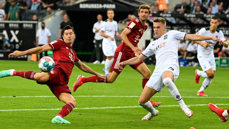 Robert Lewandowskizieht ab, Matthias Ginter versucht,den Ball abzuwehren