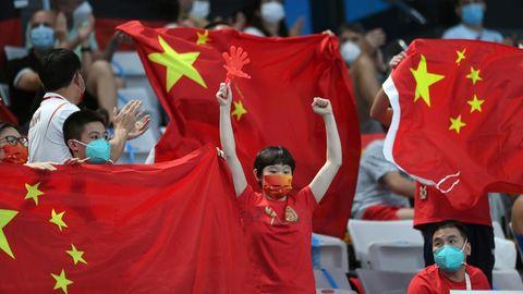 Zuschauer jubeln bei den Olympischen Spielen mit chinesischen Flaggen