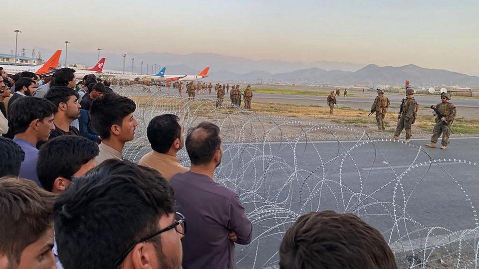 Vor zwei Rollen Nato-Stacheldraht stehen viele dunkelhaarige Männer, dahinter stehen Flugzeuge und Soldaten, die sie bewachen