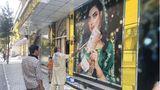 Ein Mitarbeiter eines Schönheitssalons übermaltein großes Foto einer Frau