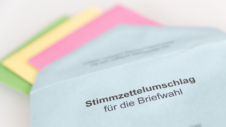 """Auf einem weißen Tisch liegt ein blauer Briefumschlag mit dem Aufdruck """"Stimmzettelumschlag für die Briefwahl"""""""