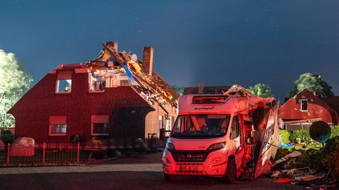 Vor einem durch einen Sturm beschädigten Haus steht ein Wohnmobil, dessen Aufbau an der Seite aufgerissen ist