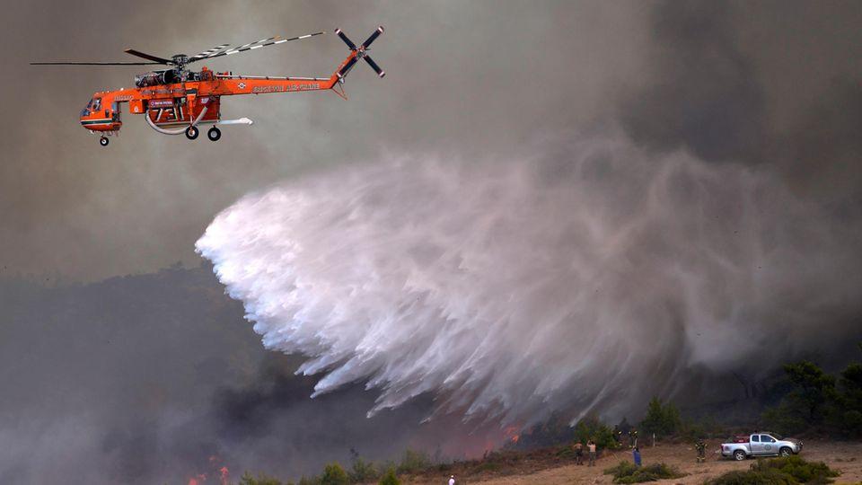 Sidérina, Grecia.  Los bomberos griegos e internacionales continúan luchando contra los incendios forestales y forestales incontrolados alrededor de Atenas.  En esta aldea, a unos 55 kilómetros al sur de la capital, un helicóptero intenta apagar las llamas arrojando agua.