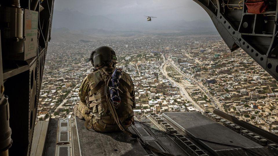 Abschied: Drei Wochen nachdem Präsident Biden den Abzug der US-Truppen bis Ende August angekündigt hat, blickt ein Soldat aus dem Hubschrauber auf Kabul