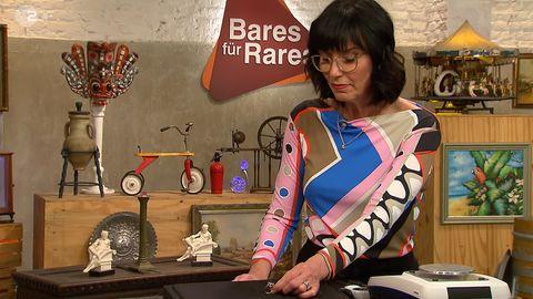 Heide Rezepa-Zabel steht im Studio von Bares für Rares und untersucht einen Ring