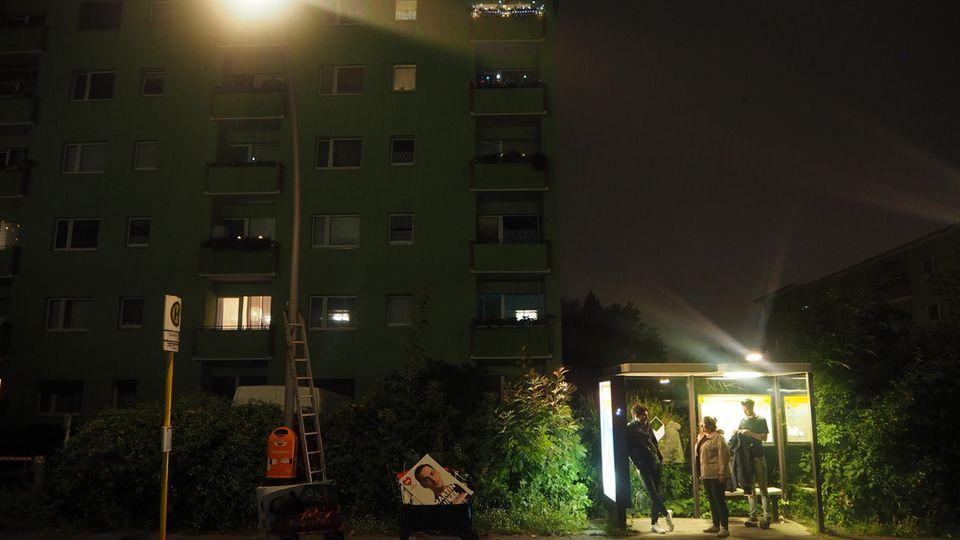 Ein Plakatier-Teams der Neuköllner SPD sucht Schutz in einer Bushaltestelle.