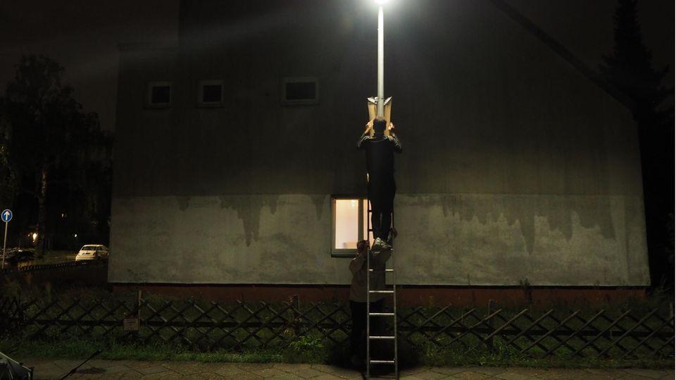 Der Juso Max von Chelstowski beim Plakatieren bei Nacht auf einer Leiter.