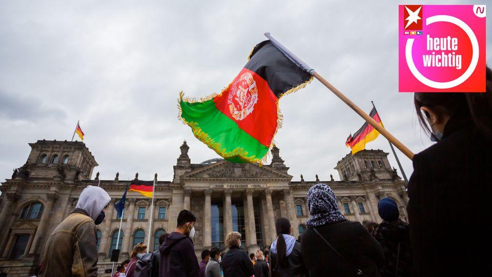 Eine Teilnehmerin hält bei einer Kundgebung vor dem Reichstagsgebäude eine Flagge Afghanistans