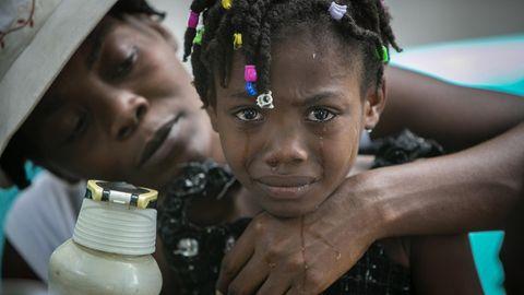 Einem farbigen Mädchen mit bunten Perlen in den Dreads laufen Tränen über das Gesicht, während eine Frau es von hinten umarmt