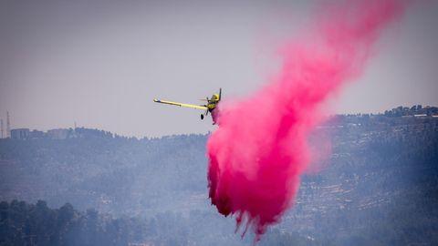 Ein gelbes einmotoriger Propellerflugzeug lässt eine Wolke pink gefärbtes Löschwasser über einem Wald ab
