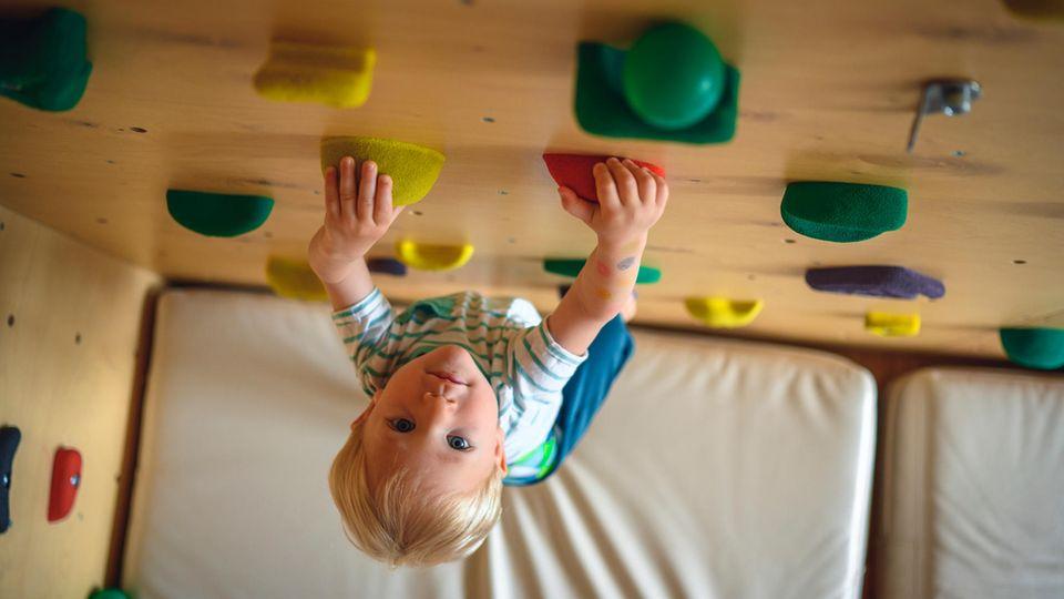 Klettersteine: Junge klettert an Indoor-Kletterwand