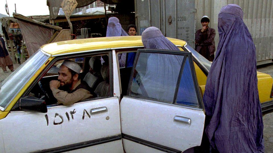 Afghanistan: Zwei Frauen in hellblauen Burkas steigen hinten in ein weiß-gelbes Taxi auf einer Straße Kabuls ein