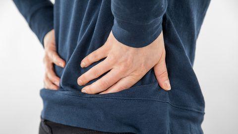 Symbolbild: Ein Mann hält sich vor Schmerzen die Hände an den Rücken.