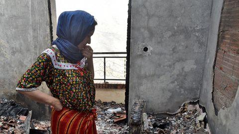 Eine Frau in traditioneller Kleidung und mit blauem Kopftuch steht mit gesenktem Kopf in verkohlten Trümmern ihres Hauses