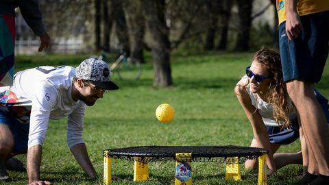 Outdoor-Spiele: Drei Erwachsene beim Spikeball spielen in einem Park