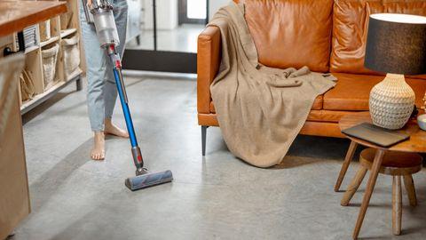 Eine Frau saugt mit dem Dyson V11 Absolute Extra ihre Wohnung.