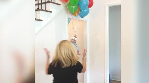 Fieser Streich: Ein Baby scheint an Heliumluftballons davon zu fliegen.