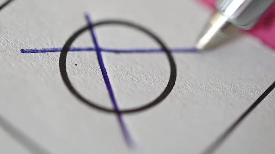 Eine Großaufnahme zeigt einen Kugelschreiber, der ein Kreuz auf einem Wahlzettel malt