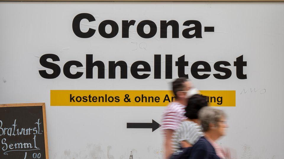 Bayern, München: Ein Schild weist am Rathaus den Weg zu kostenlosen Corona-Schnelltests