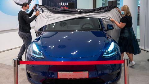 Tesla Model Y wird von zwei Mitarbeiter:innen präsentiert