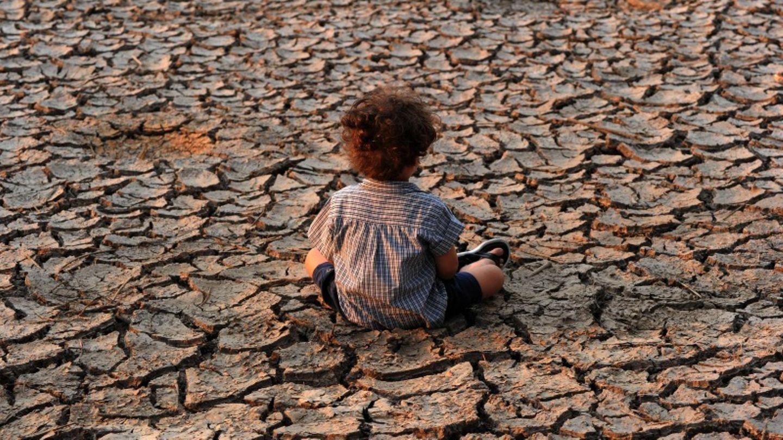 Ein Kind in Tegucigalpa sitzt auf einem verdorrten Feld.