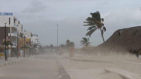 Rechts an einem Strand sind Hütten kaum noch vor verwehtem Sand zu sehen, eine Palme biegt sich im Wind. Links stehen Häuser