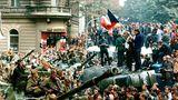 Tschechische Jugendliche stehen auf einem umgestürzten Lastwagen, während andere Prager Bürger sowjetische Panzer umzingeln