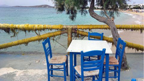 Vier blaue Holzstühle stehen auf einer Strandpromenade um einen Tisch mit weißer quadratischer Platte herum