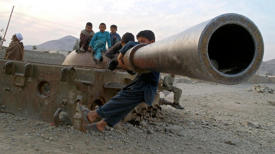 Kinder spielen auf einem alten sowjetischen Panzer in Behsood, Afghanistan