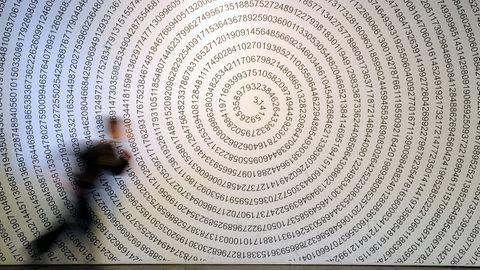 """Ein Schulkind läuft im Mitmachmuseum """"Mathematikum"""" Gießen an der auf eine Wand geschriebenen Kreiszahl Pi vorbei."""