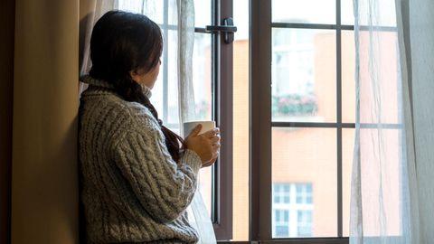 Frau hält eine Tasse und schaut aus dem Fenster