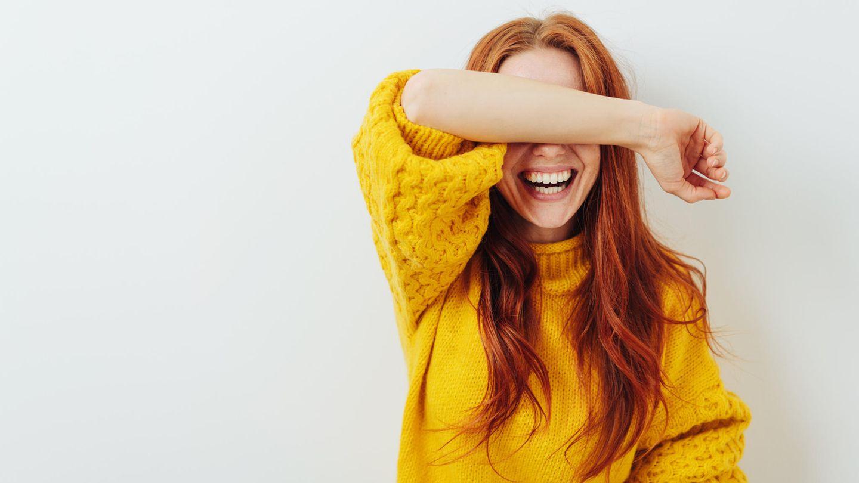 Lachende Frau mit roten Haaren hält sich einen Arm vor die Augen