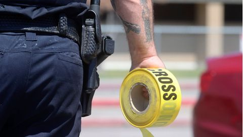 Ein Polizist hält eine Rolle mit Absperrband in der Hand